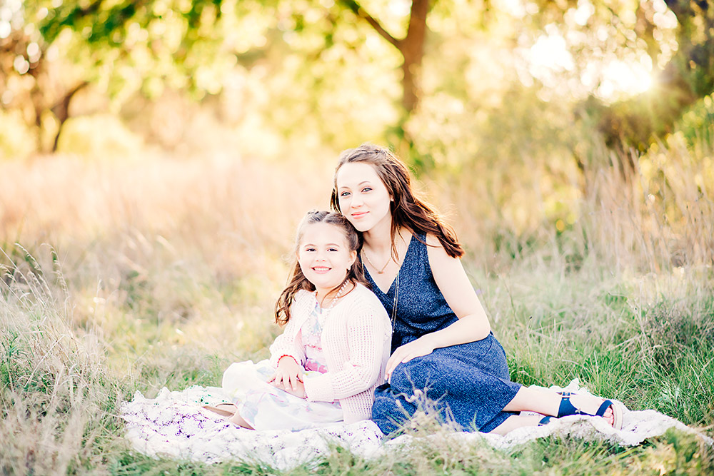 teen girl and little girl sitting on ground in san antonio texas