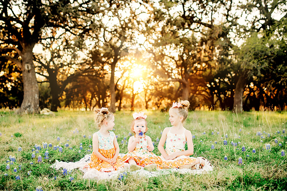 three little girls in bluebonnet field in texas hill country
