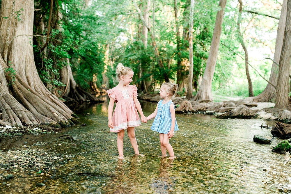 two little girls standing in a pond in san antonio texas