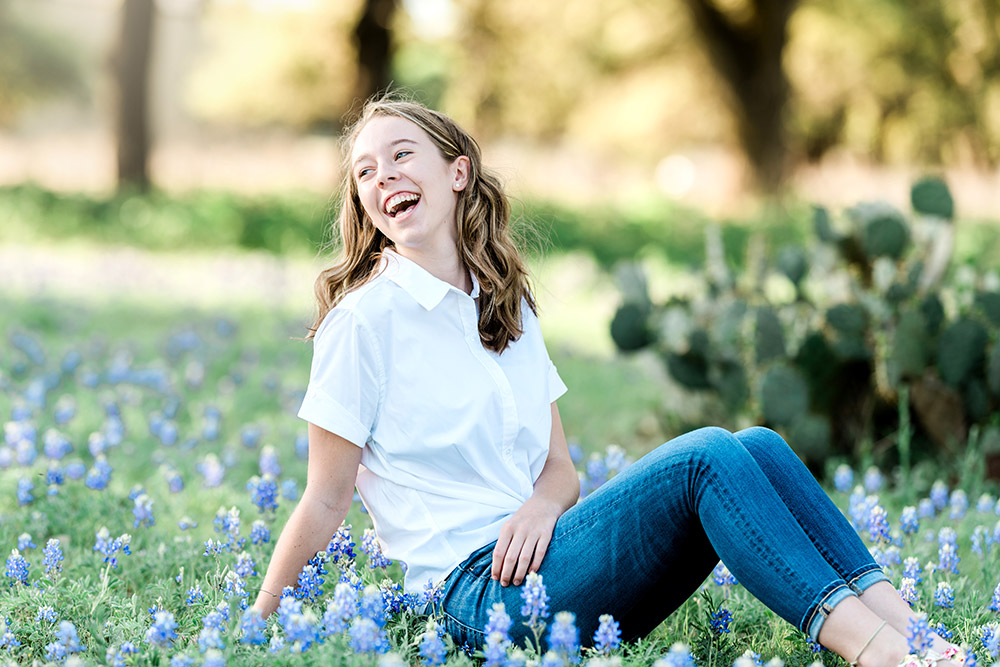 teen girl sitting in bluebonnet field in texas hill country
