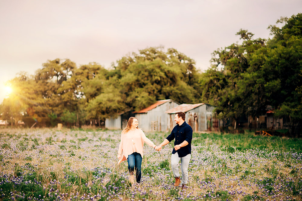 couple walking through bluebonnet field in texas hill country