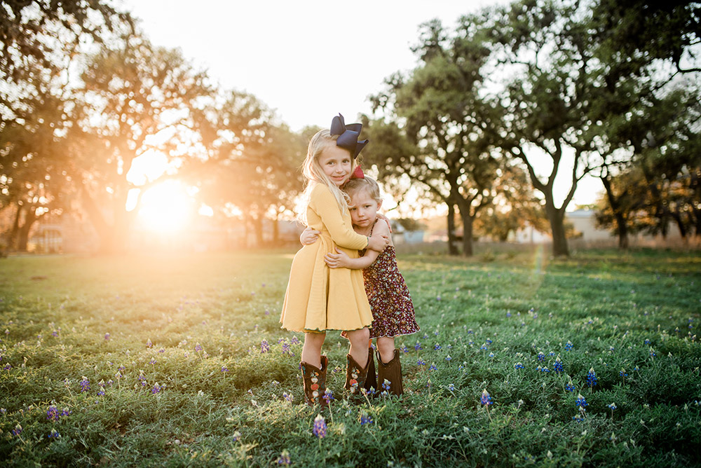 two little girls hugging in bluebonnet field in texas hill country