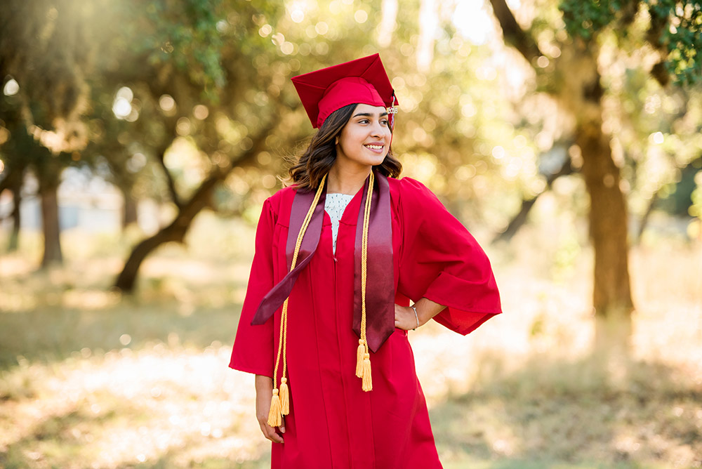 teen girl in red cap and gown in texas hill country