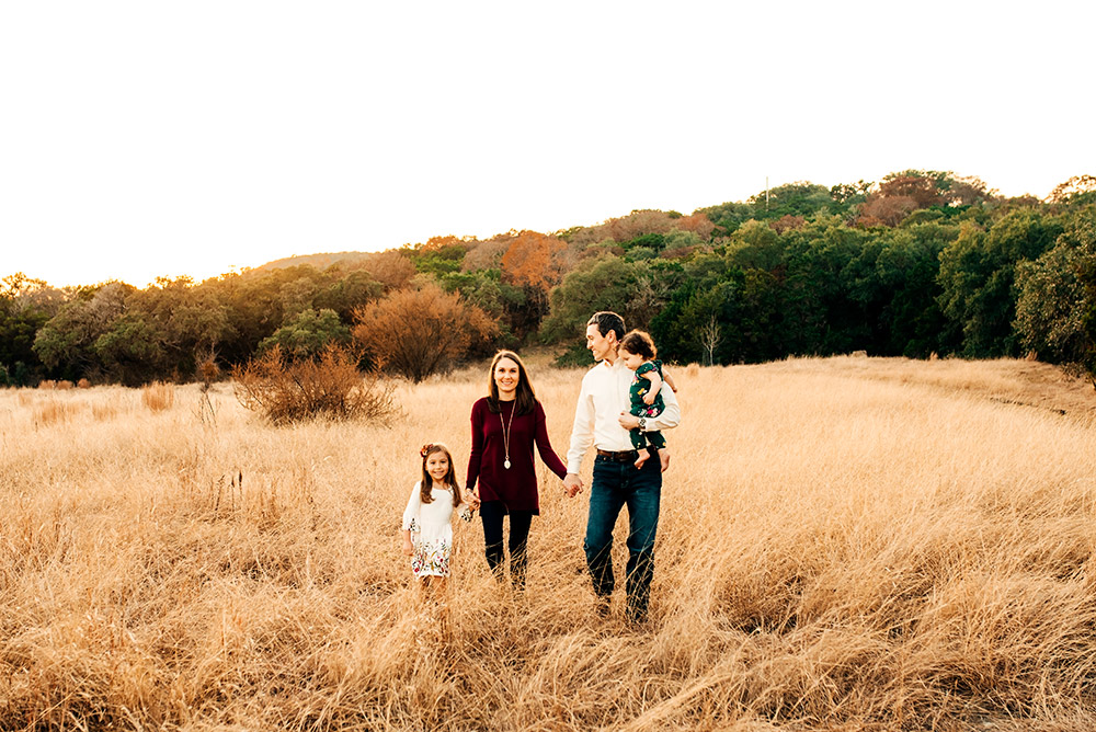 family walking through field in texas hill country