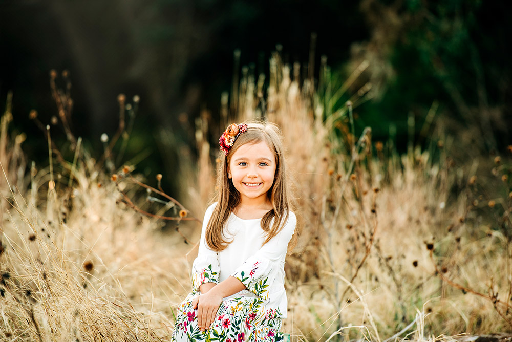 little girl sitting in field in texas hill country