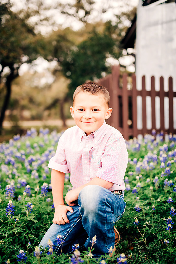 little boy in bluebonnets in texas hill country