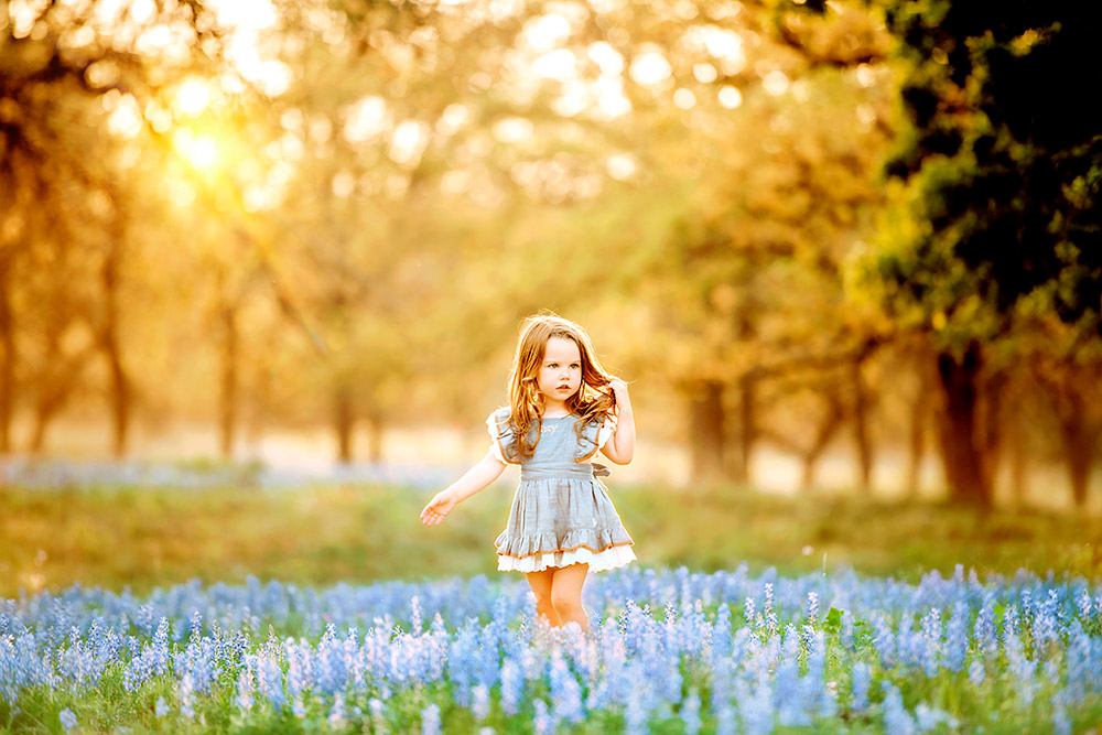 little girl in bluebonnet field in texas hill country