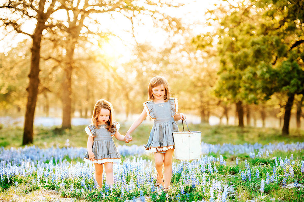 two little girls in bluebonnet field in texas hill country