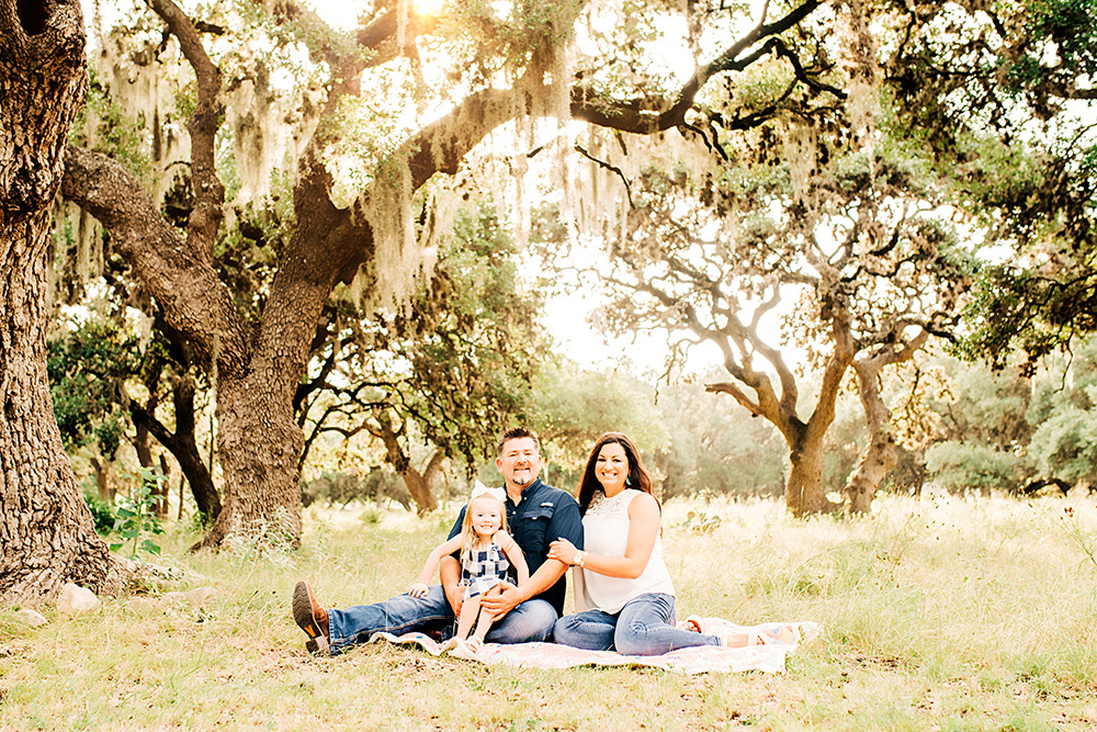 family sitting on ground in texas hill country