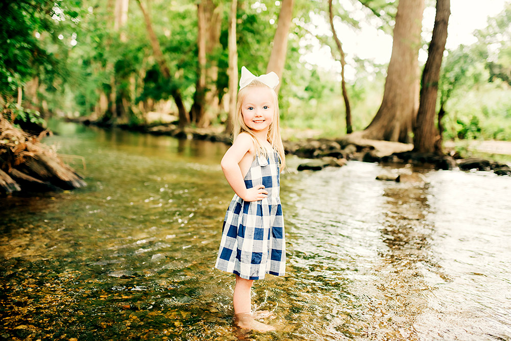 little girl standing in pond in texas hill country