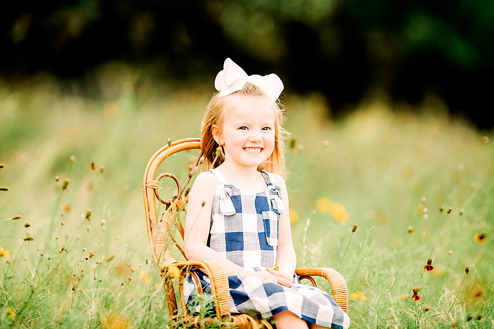 little girl sitting in chair in field in texas hill country