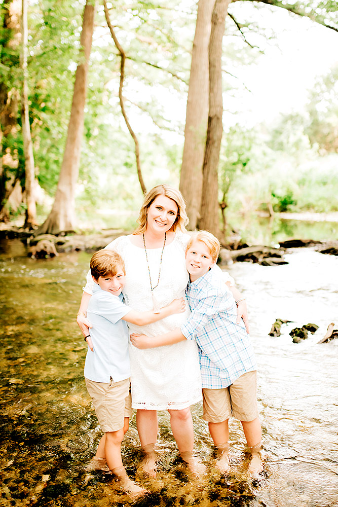 two little boys hugging mom standing in pond in san antonio texas