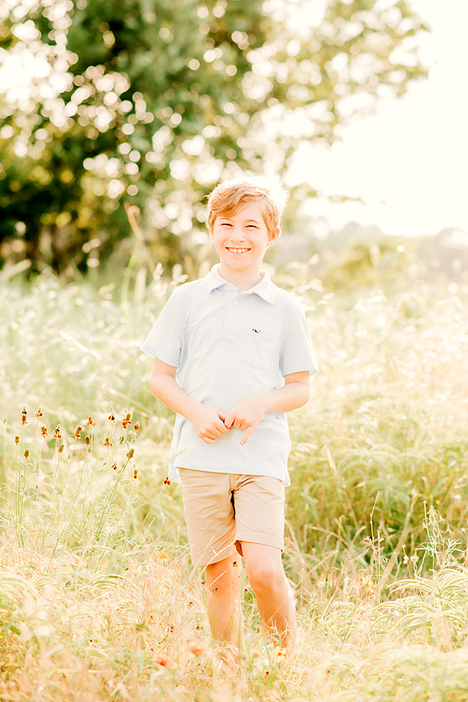 little boy standing in field in texas hill country