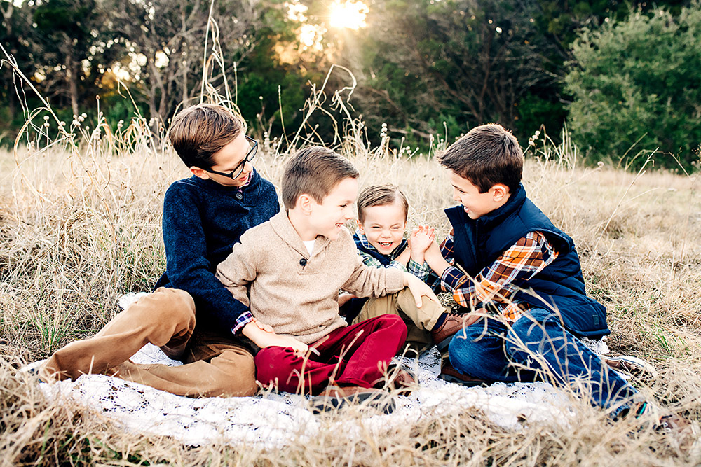 four boys laughing on ground in texas hill country