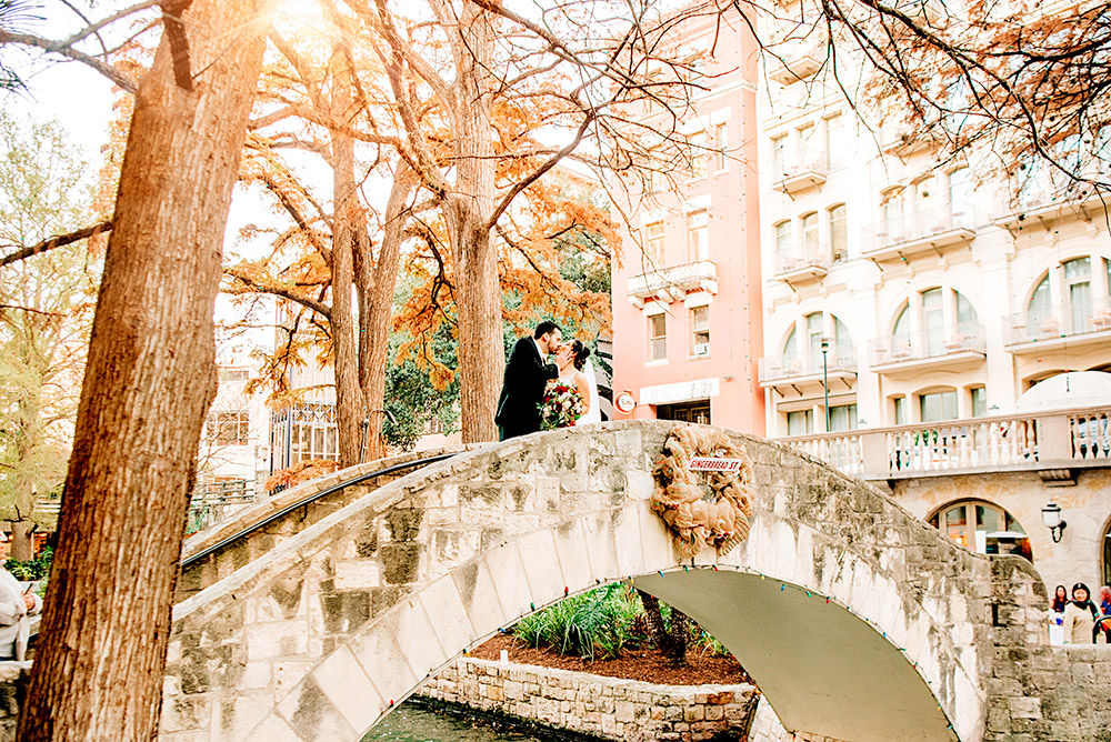 bride and groom kissing on a bridge in san antonio texas