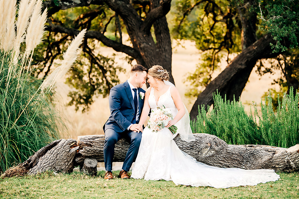 bride and groom smiling at each other in texas hill country