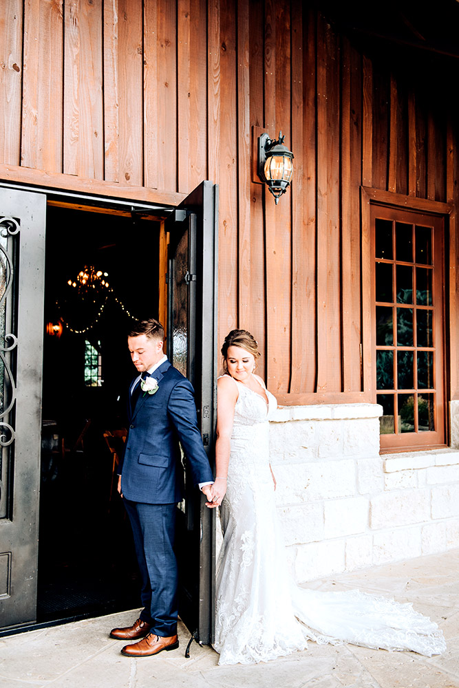 bride and groom holding hands behind door in texas hill country