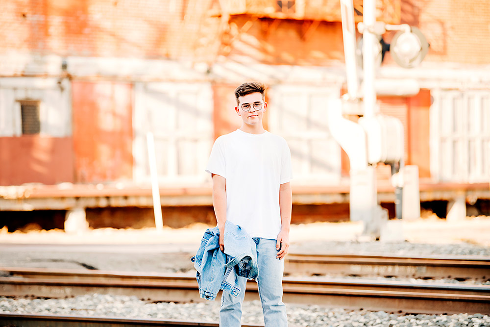 teen boy standing by railroad tracks in san antonio texas