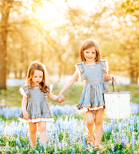 two girls in bluebonnet field in texas hill country